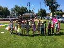 Czerwiec 2017_1 Dzieci stoją na trawie i animują kukiełkami, a moderatorka recytuje wiersz Juliana Tuwima pt.