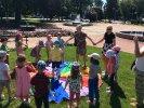 Czerwiec 2017_2 Na trawniku leży kolorowa chusta. Wszyscy stoją na około niej i się bawią.