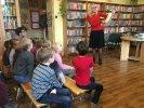 dkk grudzień_4 Dzieci siedzą na ławeczkach. Moderator stojąc przed nimi trzyma otwartą książkę i pokazuje ilustrację.