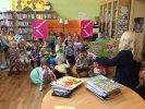 Dzieci siedzą na ławeczkach. Moderatorka siedząc przed nimi trzyma otwartą książkę i opowiada o czym ona jest..