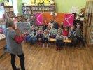 """""""Smerfne Jeże"""" bawią się i dyskutują w konstantynowskiej bibliotece _2 Dzieci siedzą na ławeczkach i odpowiadają na pytania. Moderatorka stojąc przed nimi trzyma otwartą książkę i zadaje pytania dotyczące bajki przedstawionej w Bibliotecznym Teatrzyku Kukiełkowym"""