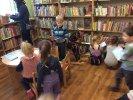 """""""Smerfne Jeże"""" bawią się i dyskutują w konstantynowskiej bibliotece _3 Dzieci przeglądają na półkach oraz stoliku biblioteczne książki."""