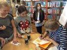 Pani Joanna wpisuje w książkach i na pamiatkowych zakładkach dedykacje i autografy dla wszystkich uczestników spotkania.