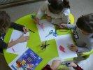 Przedszkolaki z odrysowanych swoich rączek robią Świętego Mikołaja.